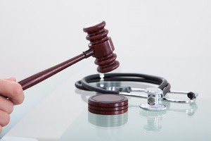 Judges gavel and a stethoscope in a conceptual image of a judgment in a medical malpractice claim